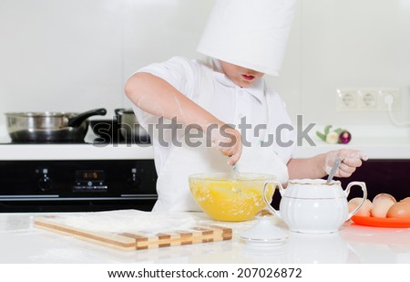 Cute little boy in a large toque standing baking almost hidden from view as the hat slides over his eyes as he mixes the eggs and ingredients in a bowl - stock photo