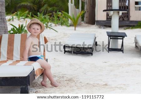 Cute little boy in a straw hat sitting on a beach chair - stock photo