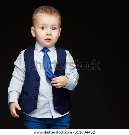 Cute little boy in blue business suit with surprised expression on face, touching his tie. Over dark background. - stock photo