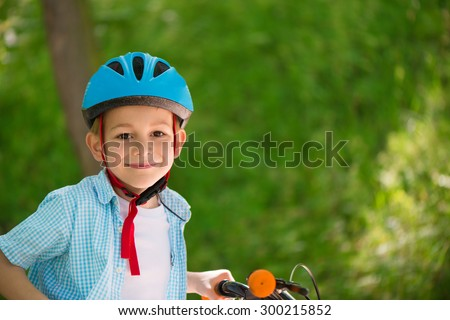Cute little boy in helmet on bike in forest - stock photo