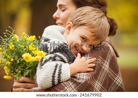 Cute little boy in his mother's arms during the walk in nature - stock photo