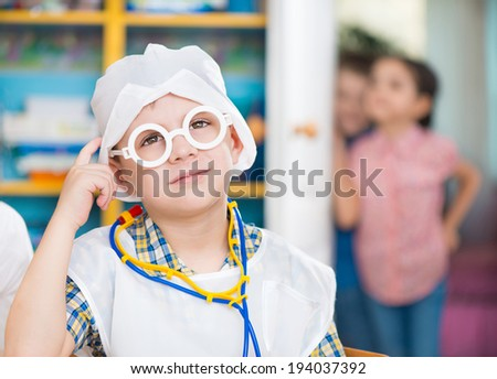 Cute little boy in medical uniform playing in doctor - stock photo