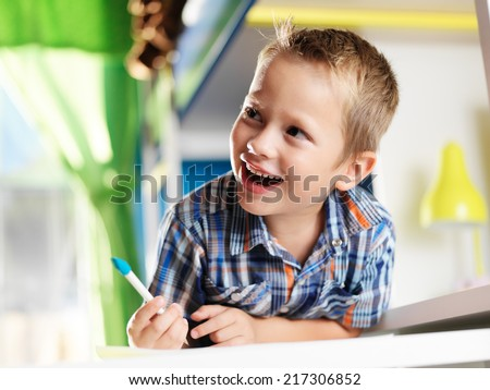 cute little boy in room studying and laughing - stock photo