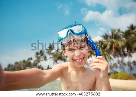 Cute little boy in snorkeling mask making selfie at tropical beach on exotic island during summer vacation - stock photo