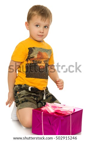 Cute little boy in t-shirt and shorts is sitting on the floor. Beside the boy lies a beautifully packaged box with a gift - Isolated on white background