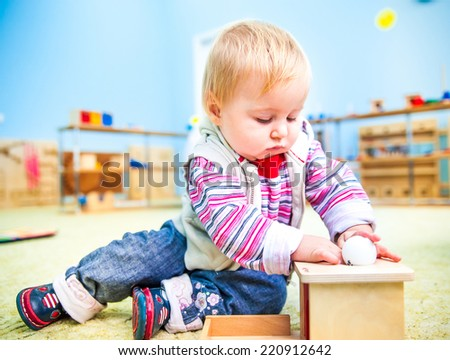 cute little boy in the classroom early development plays with numerous toys - stock photo