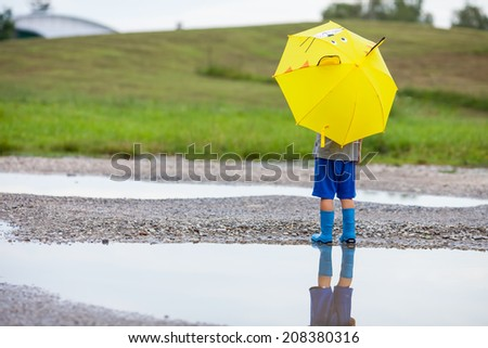 Cute little boy in the puddle with blue boots and yellow cat umbrella after the summer rain - stock photo