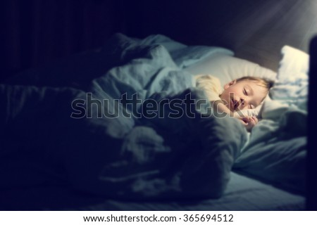 Cute little boy in yellow pyjamas is sweetly sleeping in bed with blue bed-clothes. Image with selective focus, toning and soft effects of shining light. - stock photo
