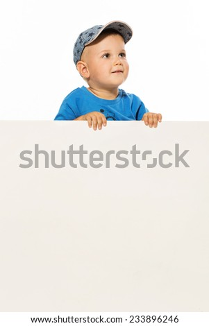 Cute little boy is above white blank poster looking up - stock photo