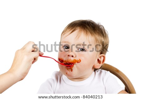 Cute little boy is being fed with jam using spoon, isolated over white.