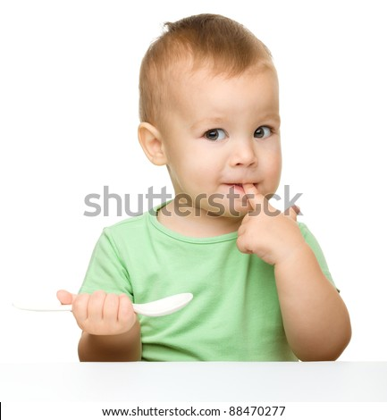 Cute little boy is biting his finger while holding a spoon and sitting at table, isolated over white - stock photo