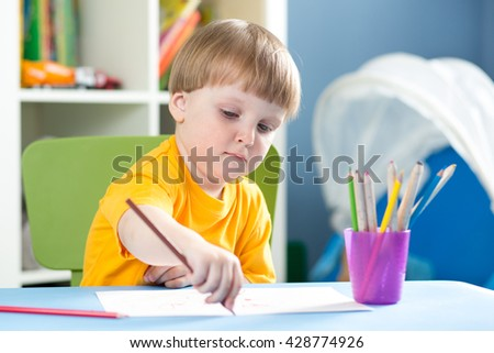 Cute little boy is drawing with color pencils in nursery
