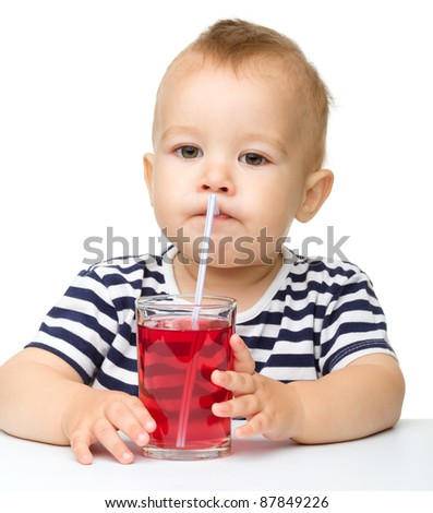 Cute little boy is drinking red juice using straw while sitting at table, isolated over white