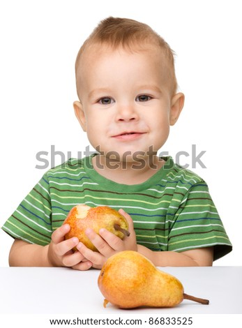 Cute little boy is eating pear, isolated over white