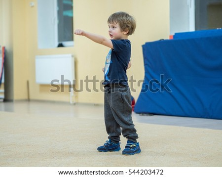 Cute little boy is engaged in martial arts. The baby kicks and punches imaginary enemy. Overall complexes exercises Kungfu.