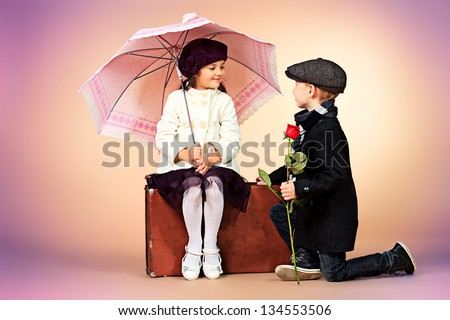Cute little boy is giving a rose to the charming little lady. Retro style. - stock photo