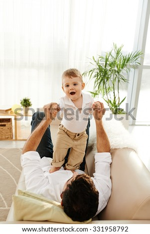 Cute little boy is happy to play with his father - stock photo