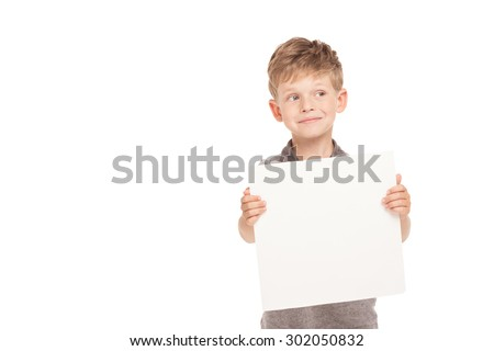 Cute little boy is isolated on white background. Boy looking aside, smiling and holding blanket paper