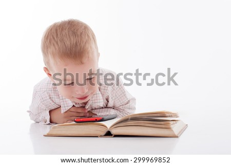 Cute little boy is lying and looking at the mobile phone with interest. The telephone is situated on the book. The kid chooses reading from new equipment. Isolated and copy space in right side