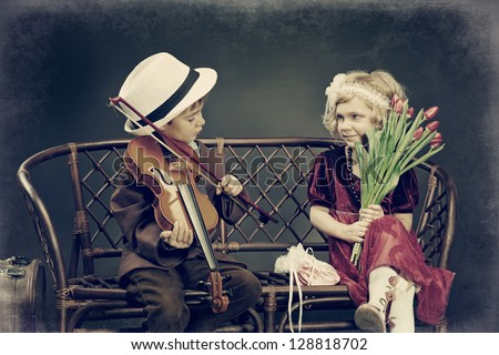 Cute little boy is playing the violin to the charming little lady. Retro style. - stock photo