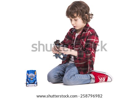Cute little boy is playing with a toys. Isolated on white background.