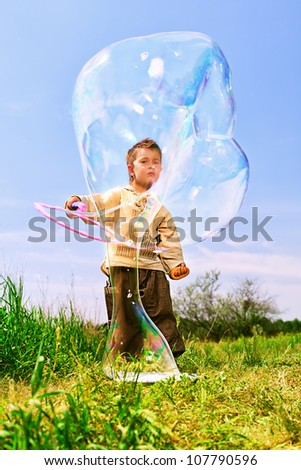 Cute little boy is playing with big bubbles outdoor. - stock photo