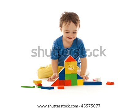 Cute little boy is playing with colorful building wooden blocks isolated on white - stock photo