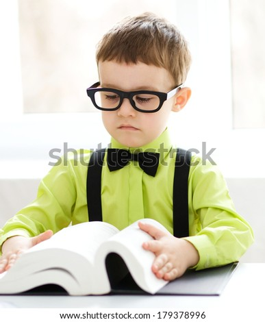 Cute little boy is reading book while sitting at table, indoor shoot - stock photo