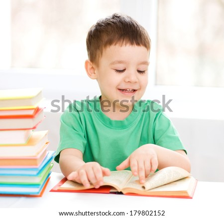 Cute little boy is reading book while sitting at table, indoor shoot
