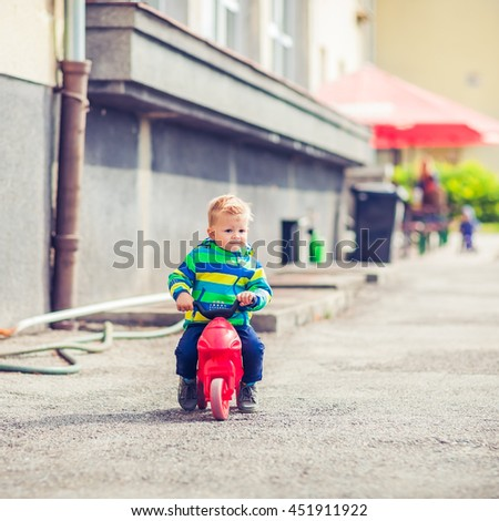 Cute Little Boy Is Riding His Three Wheels Bike on the Street