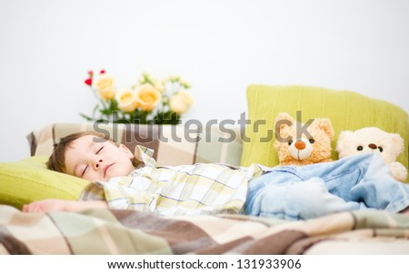 Cute little boy is sleeping next to his teddy bears - stock photo
