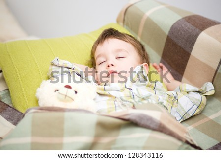 Cute little boy is sleeping with his teddy bear - stock photo