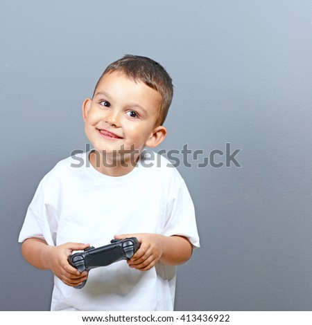 Cute little boy kid holding joystick and playing video games against gray background