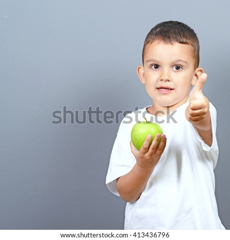 Cute little boy kid showing thumbs up for green apple against gray background  - stock photo