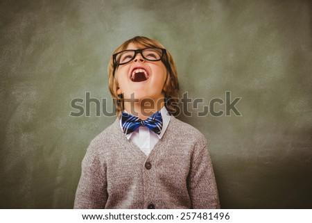 Cute little boy laughing in front of blackboard - stock photo