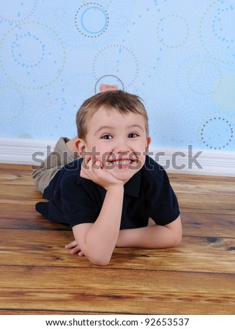 cute little boy laying on floor with hand on chin - stock photo