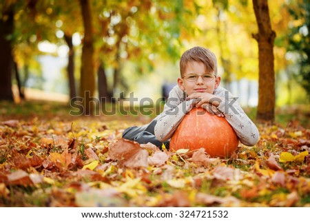 Cute little boy  leaning on a pumpkin, autumn time - stock photo