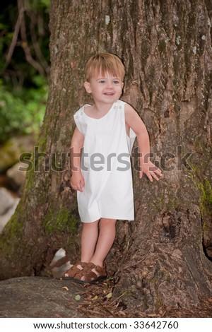 cute little boy leaning on a tree - stock photo