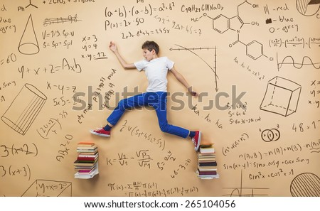 Cute little boy learning playfully in frot of a big blackboard. Studio shot on beige background. - stock photo