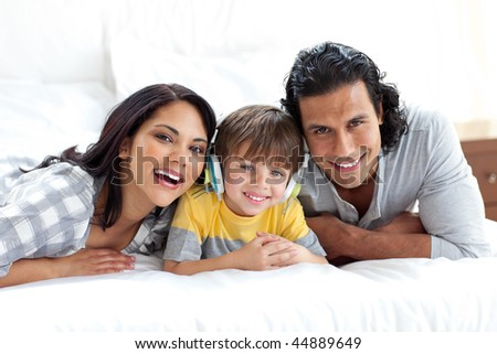 Cute little boy listening to music with his parents on a bed