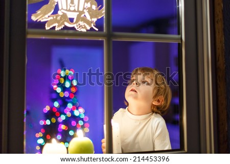 Cute little boy looking at lights window at Christmas time and holding candle. With colorful lights from Christmas tree on background, selective focus. - stock photo