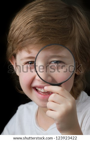 Cute little boy looking through a magnifying glass and smiling