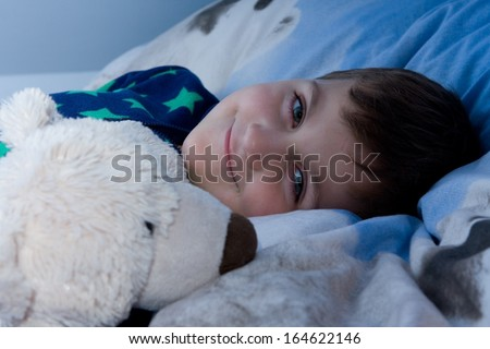 cute little boy lying in bed with plush toys
