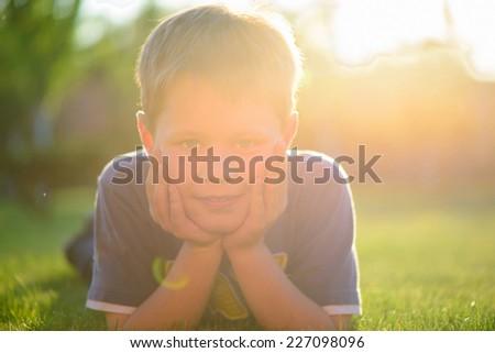 Cute little boy lying in green grass - stock photo