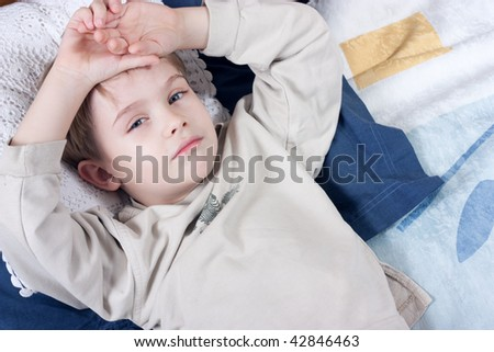cute little boy lying on the bed - stock photo