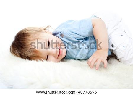 cute little boy lying on the white carpet - stock photo