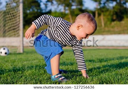 Cute little boy on a soccer field kneeling down to touch the green grass with the goalposts and ball visible behind him - stock photo