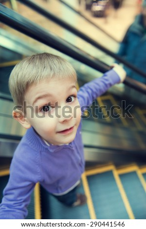 Cute little boy on escalator, funny wide-angle view.