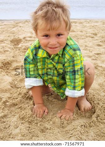 Cute little boy on the beach near the sea - stock photo
