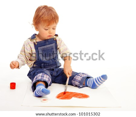 Cute little boy painting a heart shape on the paper before Valentine day - stock photo